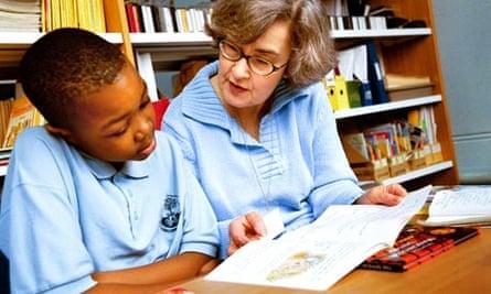 elderly lady reading to school pupil