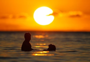 A couple watches the last rays of sunlight of 2011 off Waikiki Beach