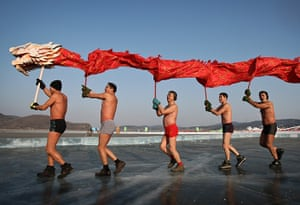 New Years day swimmers: Chinese winter swimmers perform a dragon dance on a frozen lake, Shenyang