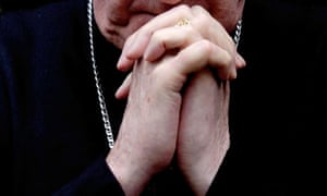 A priest's hands clasped in prayer