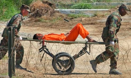 A detainee from Afghanistan is carried on a stretcher at at Camp X-Ray at Guantanamo Bay