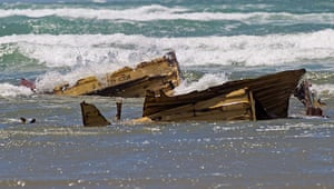 Rena breaks up: A shipping container in the waves after being washed ashore on Waihi Beach