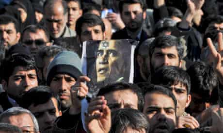 A poster of Barack Obama is held during the funeral of the killed scientist Mostafa Ahmadi-Roshan