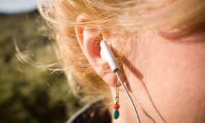 A headphone inserted into a woman's ear