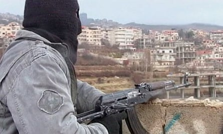 A member of the Free Syrian Army stands guard over Zabadani
