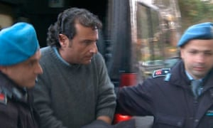 Francesco Schettino, captain of the Costa Concordia, is escorted into a prison by police officers