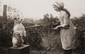 Kodak: 1920s: A girl taking a photograph of a dog