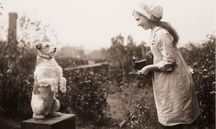 Kodak: Young girl taking a photograph of a dog, c 1920s.
