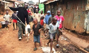 Children walk beside a man leading his sheep in the sprawling Kibera slum near Nairobi