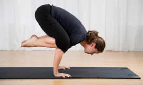 Woman on exercise mat practising yoga