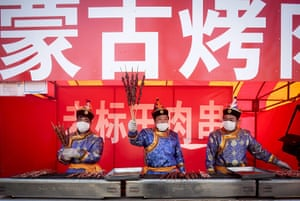 Chinese new year : Food vendors dressed in imperial costumes offer meat skewers