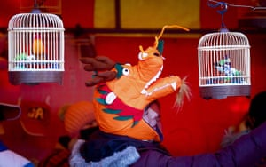Chinese new year : A vendor wearing a dragon hat reaches for a toy bird cage in Beijing