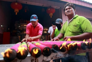 Chinese new year : Indonesian-Chinese workers set up giant joss sticks at a temple in Jakarta