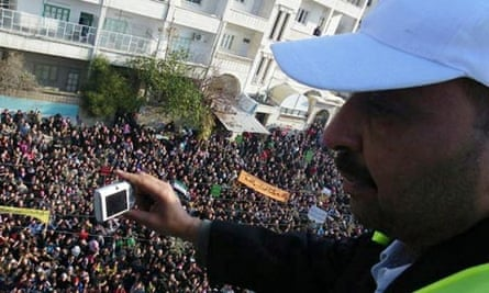 An Arab League observer takes photographs of anti-government protesters in Adlb