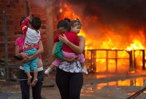 Pinheirinho favela: Residents flee as a barricade burns in the background