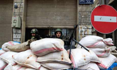 Syrian soldiers man a checkpoint in Homs