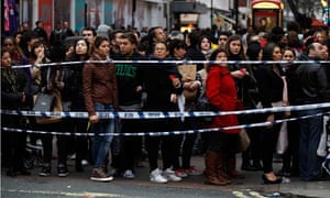 Shoppers make their way past a police cordon following a fatal stabbing on Oxford Street in London