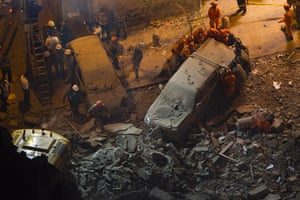 24 hours in pictures : escue workers remove a car after a building collapsed in Rio de Janeiro