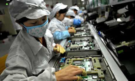 Chinese workers assemble electronic components at Foxconn's factory in Shenzhen