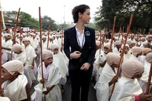 Gandhi world record event: An official of Guinness World Records, poses with boys dressed as Gandhi