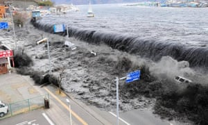 A tsunami breaches the flood barriers of Miyako city after north-east Japan is hit by an earthquake