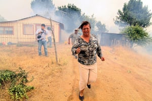 Forest fires in Chile: A woman runs from a forest fire