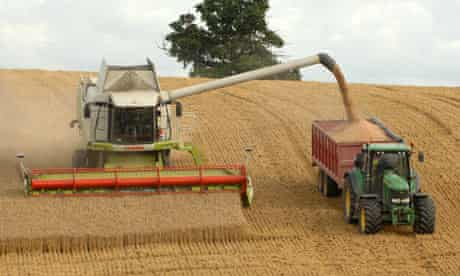 A combine harvester gathering its crop on arable farmland near Leighton in Shropshire