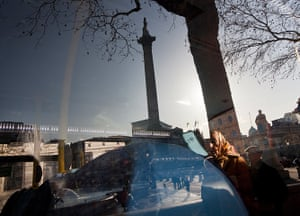 Reflections: A reflection of Trafalgar Square through the window of a passing bus