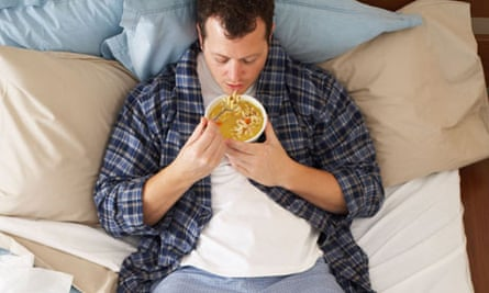Man sick in bed eating soup