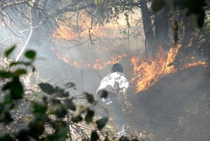 Chile forest fire: A man works to put out a forest fire near Concepcion city