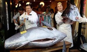 Kiyoshi Kimura, left, cuts the bluefin tuna outside his Sushi Zanmai restaurant in Tokyo