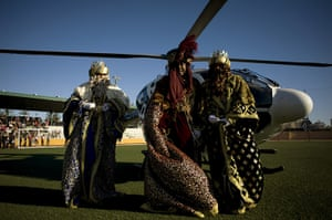 Epiphany: Men dressed as the three wise men arrive in a helicopter