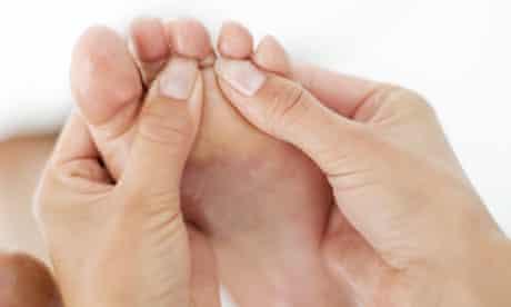 A reflexologist massages a patient's foot
