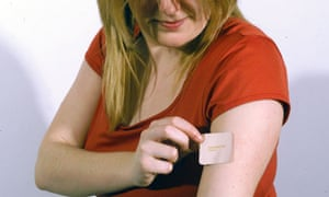 A woman applying a nicotine patch to her arm