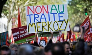 A masked demonstrator hoist a sign that  reads 'No to Merkozy treaty' for Merkel and Sarkozy, as thousands of protestors take part in a demonstration called by French leftist parties against austerity measures and the European budgetary treaty, in Paris, France, 30 September 2012