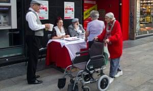 Red Cross volunteers collect money in the street, in Madrid, Wednesday Oct. 10, 2012.