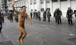 A naked protester runs through Syntagma Square by the parliament building as demonstrators clash with police while protesting against the visit to Greece by Germany's Chancellor Angela Merkel October 9, 2012 in Athens, Germany.