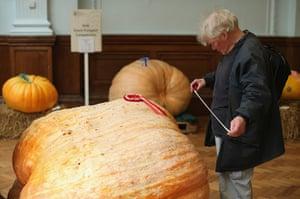 Harvest festival: A man takes a measurement of a prize-winning pumpkin