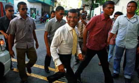 The Maldives' former president Mohamed Nasheed is escorted by police towards a court in Malé