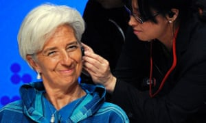International Monetary Fund (IMF) Managing Director Christine Lagarde smiles as an assistant adjusts her earphones at the start of the seminar 'Globalization at a Crossroads: From Tokyo to Tokyo' at the International Monetary Fund (IMF) and the World Bank Annual Meetings in Tokyo
