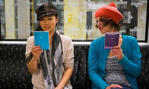 Two models on a subway using e-readers