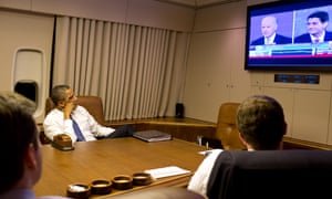 Barack Obama watches the vice-presidential debate aboard Air Force One.