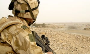 A Royal Marine watches as a mortar round lands in Gereshk in Helmand province, Afghanistan