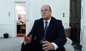 David Nicholson in a suit gesticulating sitting in a comfy chair in carpeted room