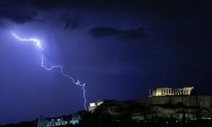Lightening illuminates the ancient Parthenon temple atop the Acropolis hill in Athens on Sunday Oct. 14, 2012.