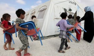 Young Syrian refugees carry their chairs into a classroom at the overcrowded Za'atari refugee camp in the Jordanian city of Mafraq.