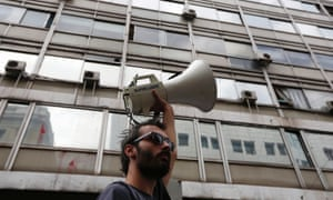 A worker raises a loudspeaker during an anti-austerity rally outside the Labour Ministry in Athens October 15, 2012.
