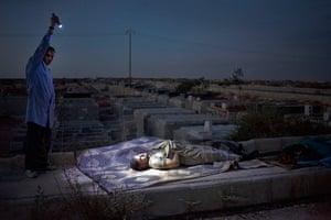 FTA: Maysun: A Free Syrian Army fighter illuminates the body of a man