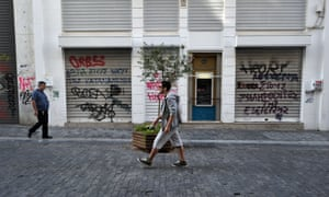 People walk by closed shops in Athens on October 18, 2012 during the 24-hours general strike.