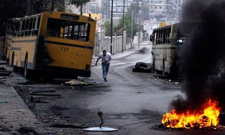 A Syrian man runs through the frontline in Aleppo